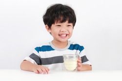 Happy Asian boy with a glass of milk, Isolated over white background.