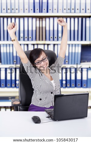 Happy Asian Business woman expressing her success by stretching her hands, shot at office