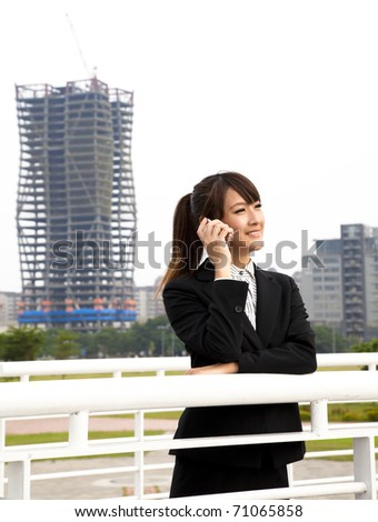 Happy asian business woman talking on the phone and office building background
