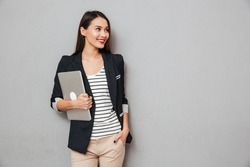 Happy asian business woman with arm in pocket holding laptop computer and looking away over gray background