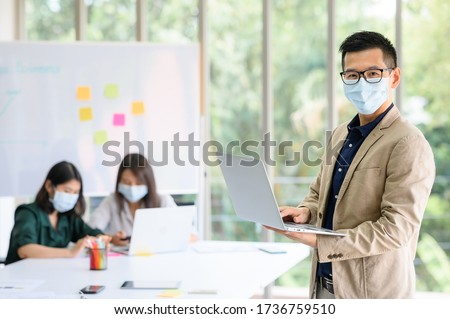 Happy Asian businessman entrepreneur wears face mask standing and holding laptop with confident, with colleague in background in meeting room at modern office