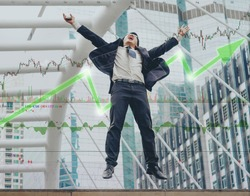 Happy Asian businessman jumping success from stock market gain much money from bullish market
