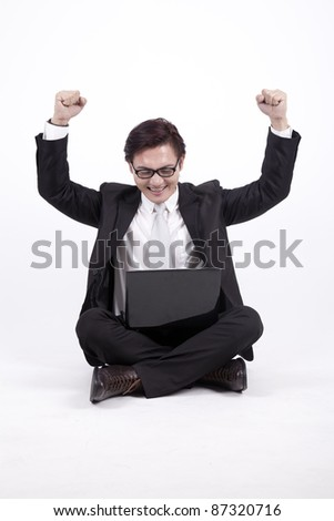 Happy Asian businessman sitting with his laptop isolated on white