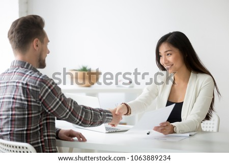 Happy asian businesswoman handshaking successful caucasian candidate holding employment agreement offering job contract, smiling friendly employer shaking new hire hand, diverse partners making deal