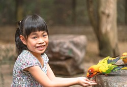 Happy Asian Child girl is feeding birds or Parrot Sun Conure in zoo of Thailand. Sitting and feeding parrots, face with big smile, eyes looking at camera.
