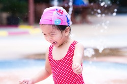 Happy Asian child girl playing water. Laughing children. Kids run around in the fountain. Baby was wearing a pink swim cap and a red bathing suit with a diamond pattern. Toddler aged 3 year old.