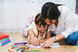 Happy Asian child kid girl kindergarten drawing teacher education to paper with parent beautiful mom at interior room home. Mother day concept