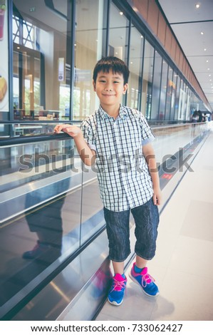 Happy asian child standing near electric speedwalk in modern airport. Handsome boy smiling and looking at camera. Travel on vacation. Vintage film filter effect. #733062427