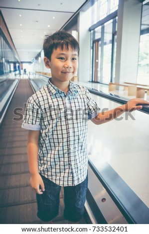 Happy asian child standing on electric speedwalk at modern airport. Handsome boy smiling happily. Travel on vacation. Vintage film filter effect. #733532401