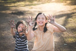 Happy Asian children playing outside with dirty hands