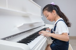 Happy Asian Chinese little girl playing classical piano in the living room at home