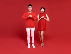 Happy asian couple in red casual attire with gesture of congratulation greeting happy new year 2021 on bright red background.
