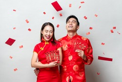 Happy Asian couple in traditional oriental costumes holding red envelopes or Ang Pao in light gray background for Chinese new year concepts, texts mean great luck great profit and everything goes well
