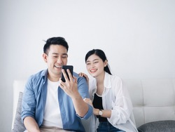 Happy Asian couple lover using laptop together at home.