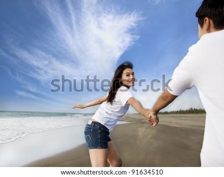 happy asian couple running on the beach