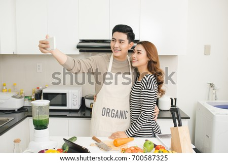 Happy asian couple smiling and cooking in the kitchen doing selfie using a smart phone - Shutterstock ID 700587325