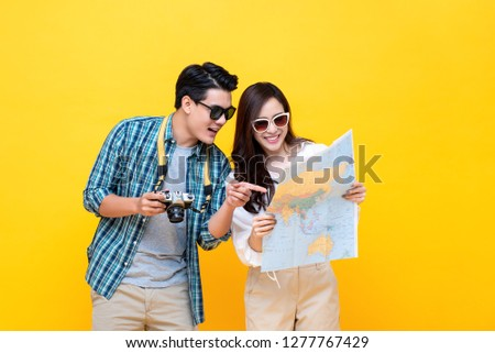 Happy Asian couple tourists looking at the map in colorful yellow background