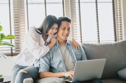 Happy Asian couple using laptop on sofa at home. Woman embracing man from behind