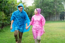 Happy Asian couple wearing a raincoat play in the rain outdoors at park.