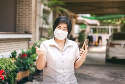 Happy asian elderly woman using mask for protect virus corona outbreak. Quarantine at home and hold smartphone use digital technology for update news and chat with family.