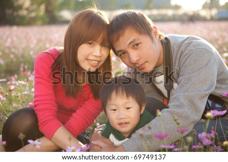 happy Asian family at a public park in warm dusk - stock photo