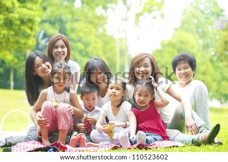 Happy Asian family enjoying picnic at outdoor park