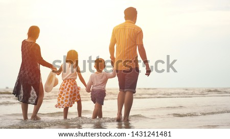 Happy asian family enjoying walk on the beach