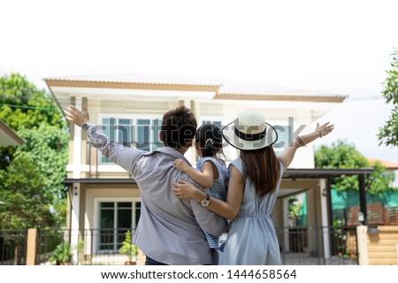 Happy Asian family. Father, mother and daughter near new home. Real estate background with copy space Foto stock ©