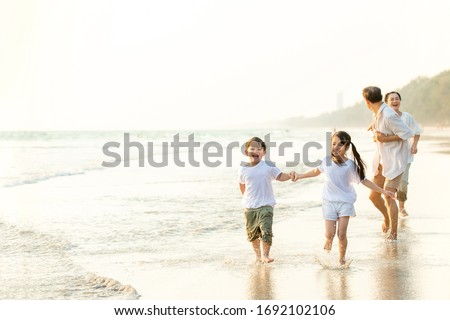 Happy Asian family grandparents with grandchild running and having fun together on the beach in summertime. Grandpa and grandma with kids relax and enjoy summer lifestyle travel holiday vacation.