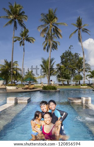 Happy Asian family having a good time at swimming pool
