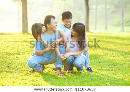 Happy Asian family having conversation at outdoor park