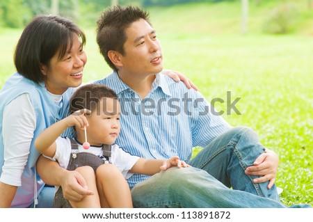Happy Asian family having fun at outdoor park
