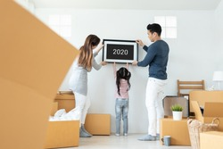 Happy Asian family holding and putting picture frame on the wall. Young Man, Woman and little kid girl decorating room together. 2020 to 2021, New Year concept. Moving house.