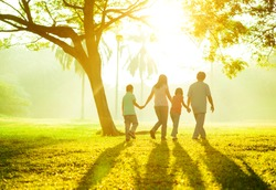 Happy Asian family holding hands walking over green lawn outdoor park, having quality time together.