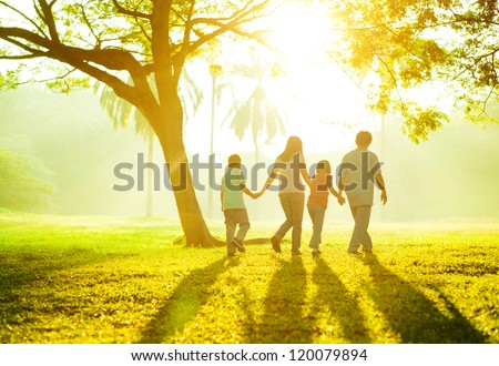 Happy Asian family holding hands walking over green lawn outdoor park, having quality time together. stock photo