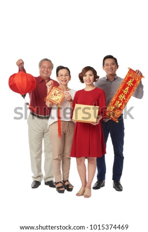 Happy Asian family holding Tet decoration, man holding scroll with best wishes inscription #1015374469