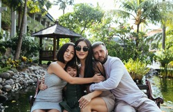 happy Asian family - husband and wife in love and their two daughters sisters hug and smile on vacation on the exotic island of Bali in Indonesia