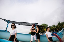 happy Asian family in black and white clothes- lovers husband and wife and their two daughters sisters are smiling and having fun on the beach near a blue boat on vacation on the exotic island of Bali