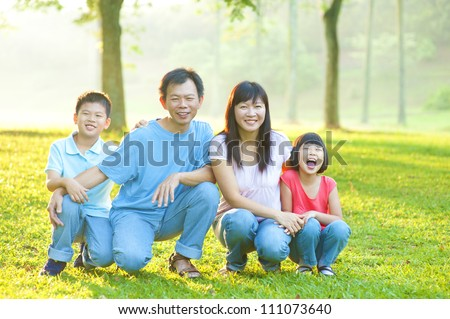 Happy Asian family in the park