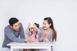 Happy Asian family inserting coins to box over white background for saving money concept