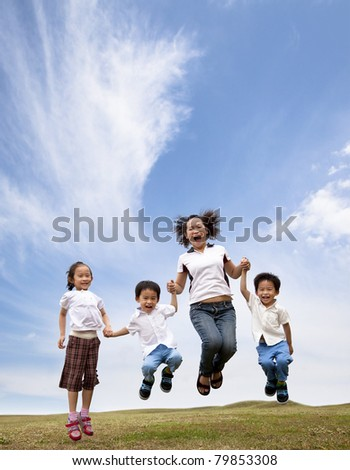 happy asian family  jumping on the grass field. mother and her children