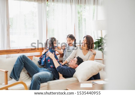 Happy Asian family playing together at sofa, home living room