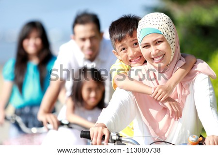 Happy asian family riding bikes in the beautiful morning outdoor - stock photo