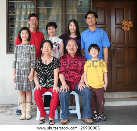 Happy Asian family smiling and taking photo at home