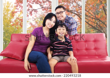 Happy asian family smiling at camera while sitting on sofa at home in autumn