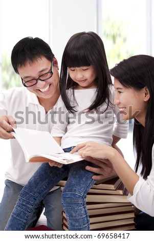 Happy asian family studying together. Parent helping daughter  reading book