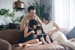 Happy Asian family using the tablet together at home.