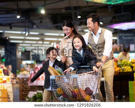 happy asian family with two children shopping in supermarket