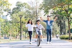 Happy Asian father and mother teach their son to ride a bicycle, Cheerful parent raise hands up in the air to support kid encouragement, family do activity together at park concept