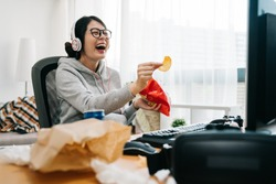 happy asian female nerd holding bag of chip snack junk food with trash on desk looking monitor laughing. relax lazy teenage girl at home watch comedy movie on computer with headset sit in messy room